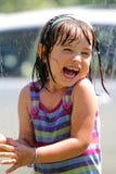 Toddler in the sprinkler. A little dark haired kindergartner girl playing in the sprinkler. Shallow depth of field Stock Images