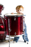 Toddler standing beside a drum Stock Photo