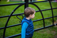 Toddler standing next to gate. Small blonde haired boy in blue jacket standing beside closed black painted wrought iron gate with grass on far side stock photography