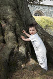 Toddler standing by tree Stock Photos