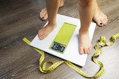 Toddler standing on weight scale in front of his mother, diet recommendation text on scale stock images