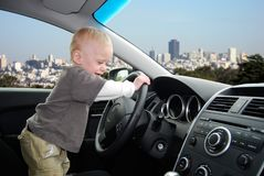 Child Pretends to Drive Car in Big City. Toddler stands up in parked car holding the steering wheel as he pretends to drive car with the San Francisco skyline in royalty free stock images