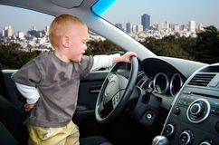 Child Pretends to Drive Car in Big City. Toddler stands up in parked car holding the steering wheel as he pretends to drive car with the San Francisco skyline in royalty free stock photos