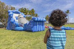 A toddler stands very still watching a bounce house inflate royalty free stock photography