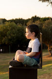 Toddler staring at the sunset. Cute Toddler boy sitting on a chair and staring at the sunset Stock Images