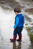 Toddler steps into a puddle. Toddler wearing blue quilted jacket, blue jeans and colorful Wellington boots stepping into a puddle making circular ripples as he royalty free stock images