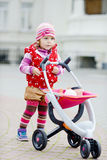 Toddler and stroller Stock Images