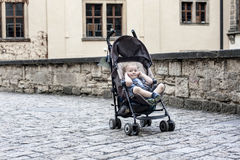 Boy close ears. Toddler in stroller waiting parents on street of old europe city. Boy close ears Stock Image