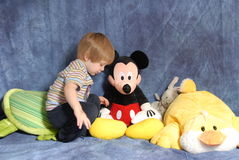 Toddler with stuffed animals. A two year old sitting with stuffed animals stock photography