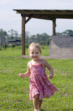 Toddler in sundress running on farm Stock Photos