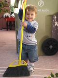Toddler Sweeping. A toddler sweeping up and cleaning the backyard Royalty Free Stock Images