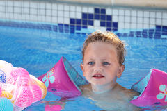 Toddler swimming. Pretty young toddler swimming in a pool with armbands to support her Stock Photo