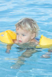 Toddler in swimming pool. 2years old toddler floating with his arm bands in a swimmimg pool Stock Image