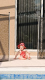 Toddler Swimming Pool Safety. A young baby sits in the opening of the safety fence left open near a swimming pool. No adults appear to be near the child looking Royalty Free Stock Photo