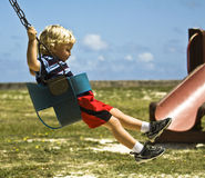 Toddler on a swing. Toddler at the village playgroung playing on a swing Stock Photos