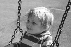 Toddler on a swing. Young boy, smiling and having fun, at the playground Stock Photos