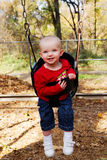 Toddler in swing. Happy toddler in infant/toddler swing at park stock photos