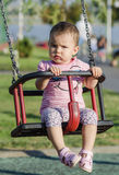 Toddler on swing. Little girl playing in park on swing Royalty Free Stock Photo