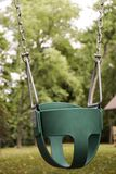 EMPTY CHILDS TODDLER SWING ON CHAINS. A toddler swing in a park waits for a child to have fun and enjoy the freedom that flying gives royalty free stock photography
