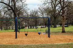 Toddler swings in city park with park bench, person walking and birds and squirrel and a few cars in the background - selective fo stock photos