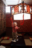Toddler on a table. Toddler playing with chandelier in an asian restaurant Stock Photo