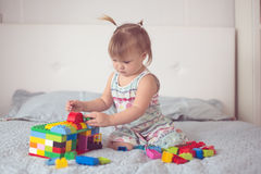 Toddler with tails play with constructor lifestyle Stock Photos