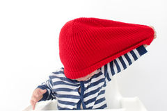 Toddler takes off hat in red cap over face studio Stock Photo