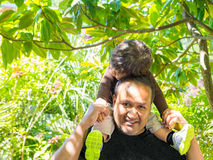 Toddler Takes A Rest On Dad's Shoulders. Son takes a short rest on dad's shoulders and head royalty free stock photography