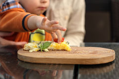 Toddler Takes Slice Of Tomato Royalty Free Stock Photos