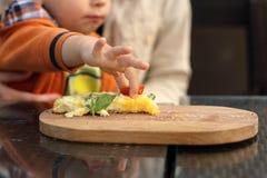 Toddler takes slice of tomato Royalty Free Stock Photos