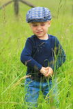 Toddler in tall grass wearing a flat cap. A toddler walking in a country field of tall grass wearing a flat cap Stock Photography
