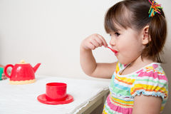 Toddler Tea Party. Young girl sips tea from her spoon at the tea party Stock Photos