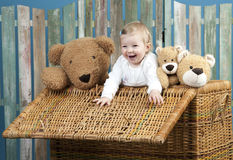 Toddler with teddy bears standing in a trunk Stock Images