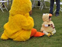 Toddler in a Rubber Duck Costume and the Rubber Duck Mascot share a moment at the Rubber Duck Festival. Rubber Duckies abound at the 16th Rubber Ducky Festival royalty free stock images