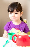 Toddler Thinking At Tea Time Stock Photo