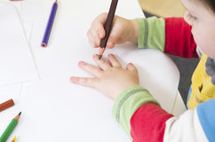 Toddler about to draw an outline of his hand. Toddler draws an outline of his hand using a brown pencil Royalty Free Stock Photography