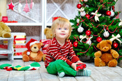 Toddler with toy car by the Christmas tree Royalty Free Stock Photo