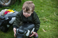 Toddler with toy cow. A toddler with a toy cow in the garden stock images
