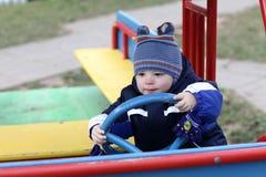 Toddler and toy iron car Stock Photos
