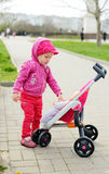Toddler with toy stroller Royalty Free Stock Photo