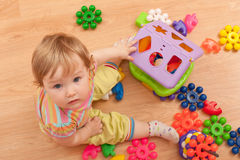 Toddler among toys. A little girl sitting on the floor is playing her toys Royalty Free Stock Photos