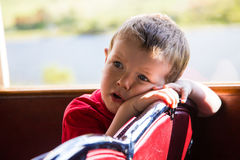 Toddler in train. A toddler looking over the back of the seat in a train stock photo