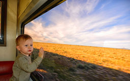 Toddler on a train ride with hands on window Stock Photos