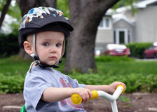 Toddler on Tricycle. A toddler wearing a helmet experiments with a tricycle Stock Image