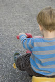 Toddler on Tricycle Back View. 3 year old boy riding a colorful tricycle from the rear Stock Image