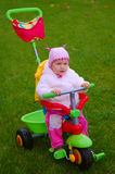 Toddler on a Tricycle. Mother and baby taking and afternoon walk in the park Stock Image