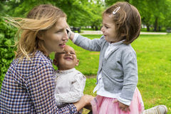 Toddler using a smartphone. Cute toddler holding a smartphone to mother's ear Stock Photography