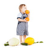 Toddler with vegetables eating orange Royalty Free Stock Image
