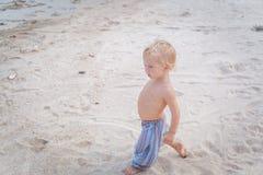 Toddler walking on a beach Stock Image
