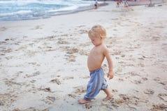 Toddler walking on a beach Stock Photo
